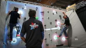 guy watching others play interactive game on valo climb wall